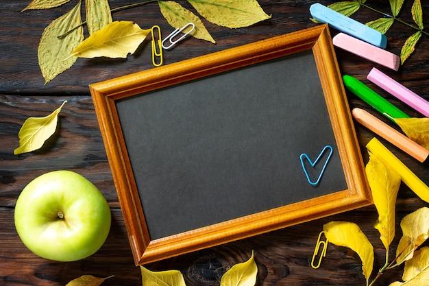 Tavolo con foglie autunnali blocco note mela e materiale scolastico spazio libero per il testo