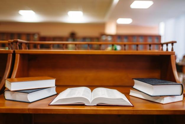 Tavolo con libri in sala di lettura, interno della biblioteca universitaria, nessuno. deposito di conoscenza, concetto di educazione