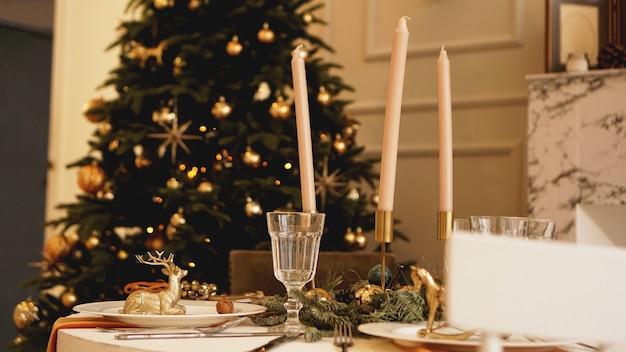 Tavolo con candele servite per la cena di natale in soggiorno, vista ravvicinata