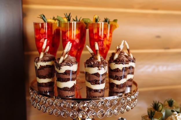 Tavolo con dolci colorati e chicche per il ricevimento della festa nuziale, tavolo da dessert decorazione. deliziosi dolci a buffet di caramelle. tavolo da dessert per una festa. torte, cupcakes. messa a fuoco selettiva.