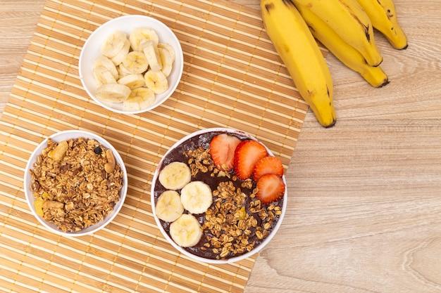 Tavolo con una deliziosa ciotola di acai, con banana, fragola e muesli.