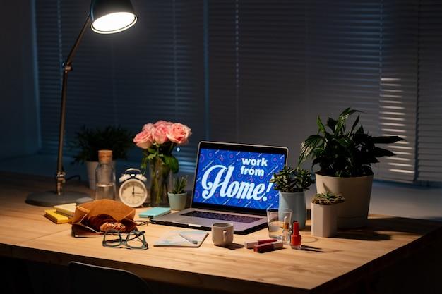 Tavolo con laptop, fiori, cibo e bevande, articoli per il trucco, quaderno, occhiali da vista, sveglia e lampada su tutta quella roba nell'oscurità