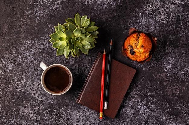 Tavolo con blocco note, fiori e caffè