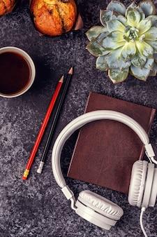 Tavolo con blocco note, cuffie e caffè