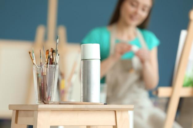 Tavolo con strumenti di pittura e spray aerosol nel laboratorio dell'artista