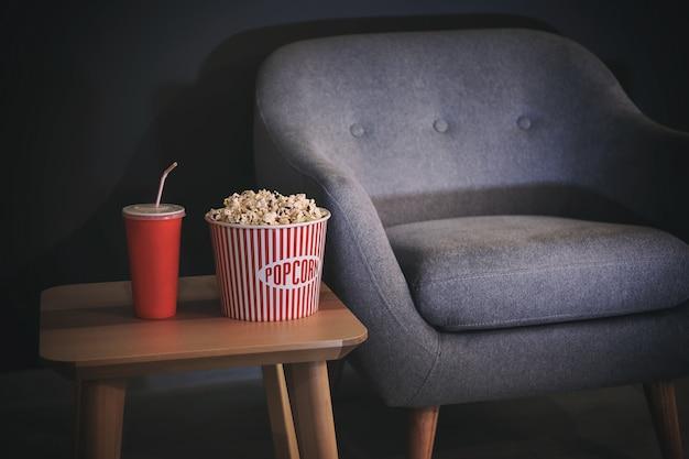 Tavolo con popcorn e drink vicino a una comoda poltrona al chiuso. home cinema