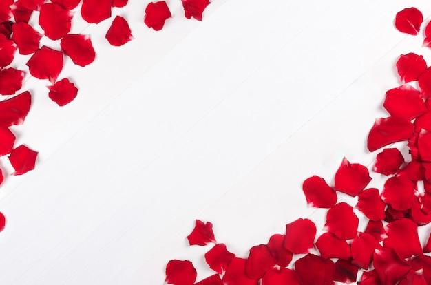 Tavolo con petali di rose rosse sul tavolo di legno bianco
