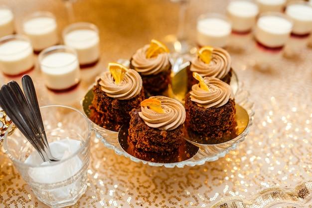 Tavolo con dolci e golosità per il ricevimento di nozze, tavolo da dessert decorato. deliziosi dolci a buffet di caramelle. tavolo da dessert per una festa. torte, cupcakes.