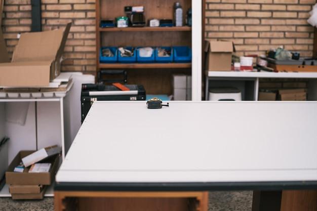 Tavolo con un metro a nastro su di esso in un'officina