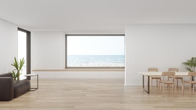 Tavolo sul pavimento di legno della grande sala da pranzo vicino alla zona giorno e divano in una moderna casa sulla spiaggia o hotel di lusso.