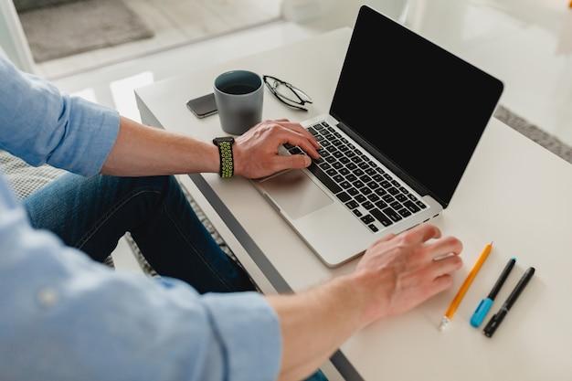 Tavolo sul posto di lavoro primo piano uomo mani a casa lavorando digitando sul computer portatile