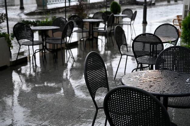 Tavoli e sedie di un caffè di strada bagnati dalla pioggia