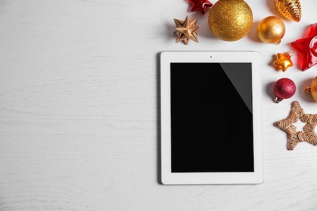 Tablet e decorazioni natalizie su fondo in legno bianco