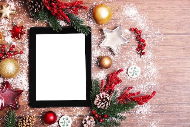 Tablet e decorazioni natalizie su fondo in legno