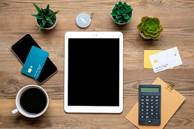 Carta di debito tablet per acquisti, ordini, tazza di caffè, smartphone, piante grasse sul tavolo in legno vista dall'alto lista della spesa per le vacanze laici, black friday, piccole imprese, concetto di negozio online piatto lay.