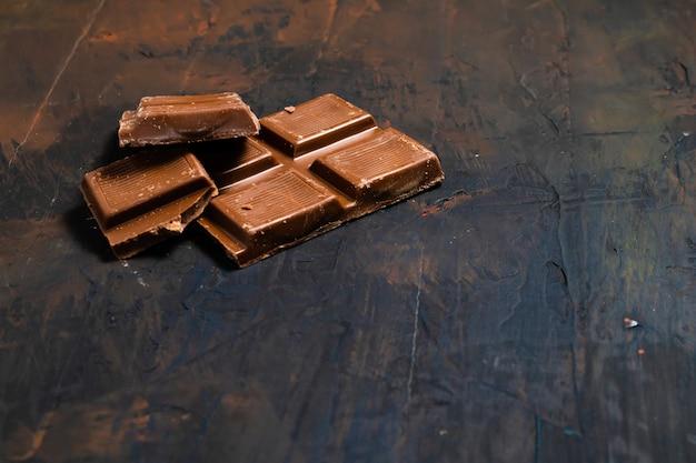 Pezzi di tavoletta di cioccolato fondente su una superficie scura. spazio per il testo.