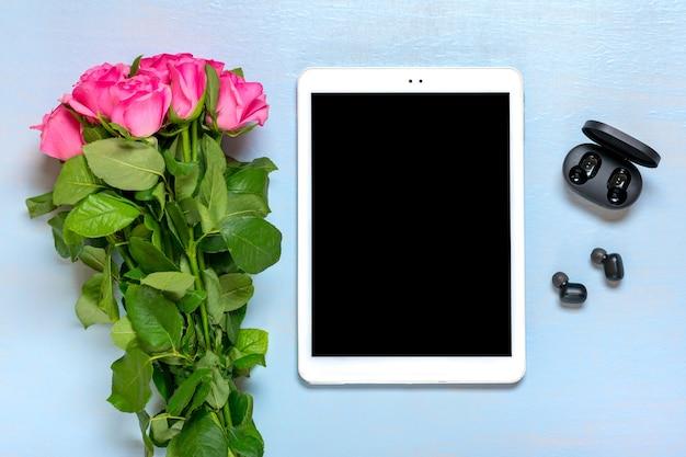 Tablet, auricolari wireless, bouquet di rose sul tavolo blu