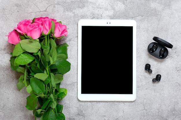 Tablet, auricolari wireless, bouquet di rose sul tavolo di cemento grigio