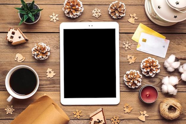 Tablet con schermo nero, tazza di caffè, carta di debito, decorazioni natalizie, fiocchi di neve sul tavolo di legno
