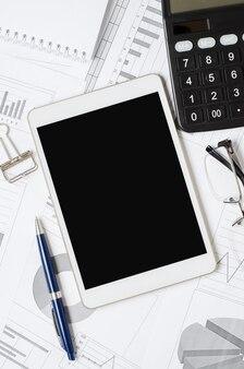 Tablet con uno schermo vuoto sullo sfondo di tabelle e grafici. il concetto di investimento online o processi aziendali. copia spazio.