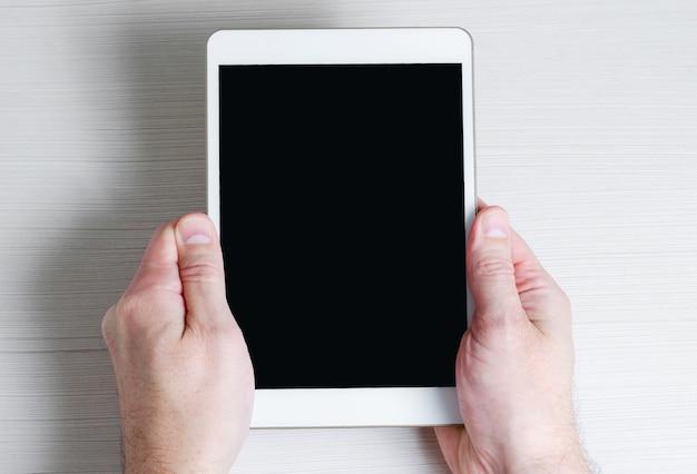 Un tablet con uno schermo vuoto nelle mani di un uomo. copia spazio.