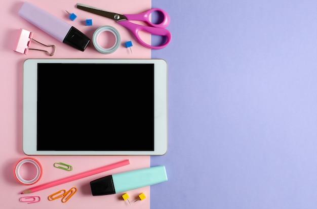 Un tablet con uno schermo vuoto e forniture per ufficio su uno sfondo colorato pastello