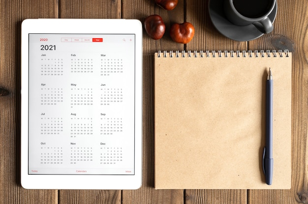 Un tablet con un calendario aperto per l'anno 2021, una tazza di caffè, castagne e un taccuino di carta artigianale su uno sfondo di tavola di assi di legno