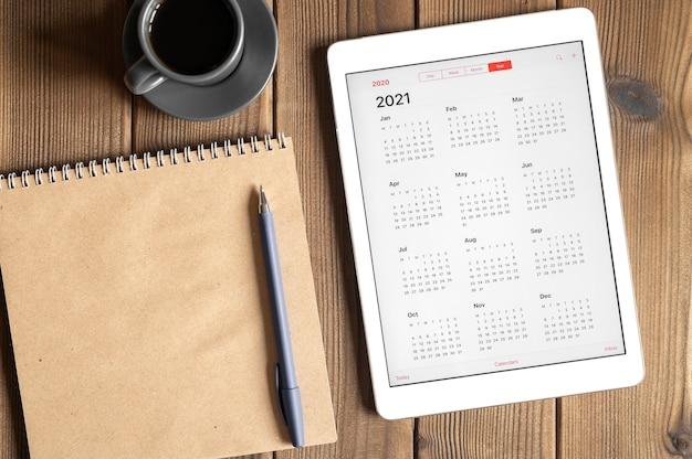 Un tablet con un calendario aperto per l'anno 2021, una tazza di caffè e un taccuino di carta artigianale