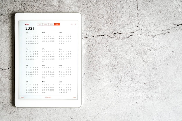 Un tablet con un calendario aperto per l'anno 2021 su uno sfondo grigio