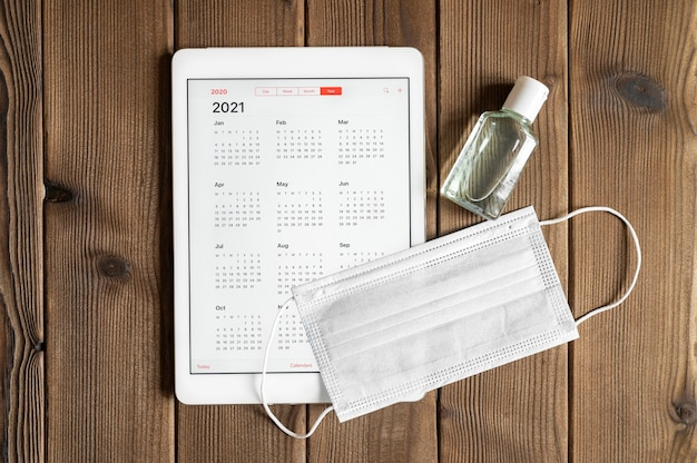 Un tablet con un calendario aperto per l'anno 2021 e maschera medica protettiva e disinfettante per le mani su uno sfondo di tavola di assi di legno. concetto di protezione dal coronavirus covid-19 nel 2021.