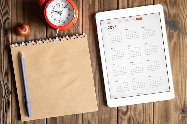 Un tablet con un calendario aperto per l'anno 2021, una sveglia rossa, castagne e un taccuino di carta artigianale su uno sfondo di tavola di assi di legno