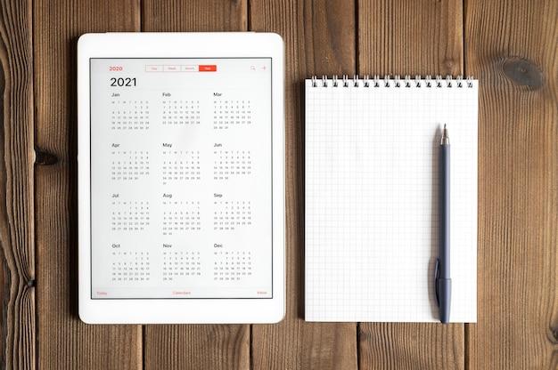 Un tablet con un calendario aperto per l'anno 2021 e un taccuino di primavera con una penna su uno sfondo di tavola di assi di legno