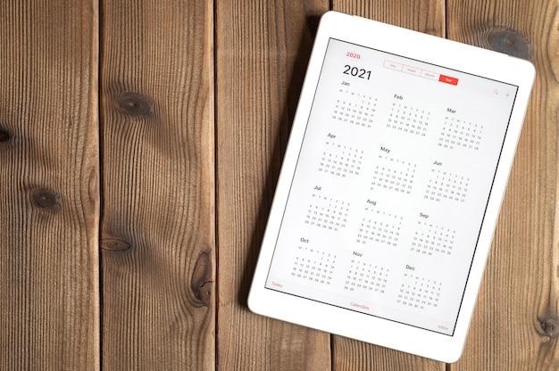 Un tablet con un calendario aperto per l'anno 2021 su uno sfondo di tavola di assi di legno. spazio per il testo