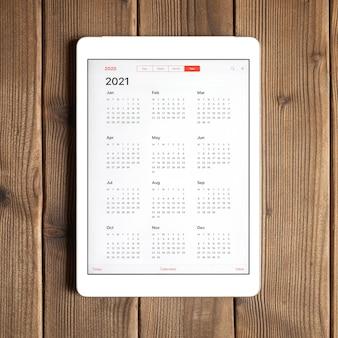 Un tablet con un calendario aperto per l'anno 2021 su uno sfondo di tavola di assi di legno. piazza