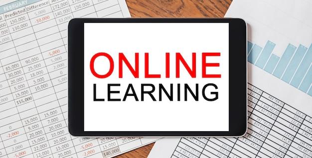 Tablet con testo di apprendimento online sul tuo desktop con documenti, report e grafici. concetto di affari e finanza