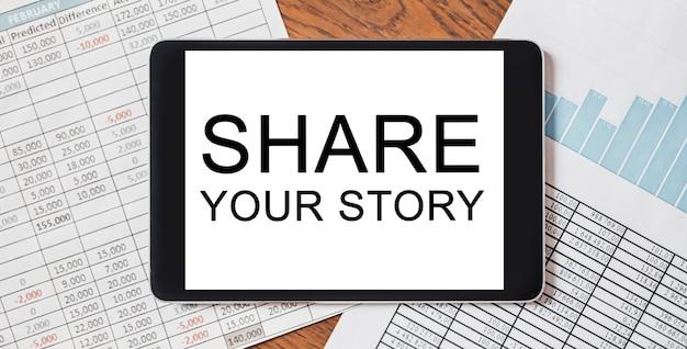 Tablet con testo condividi la tua storia sul desktop con documenti, report e grafici. concetto di affari e finanza
