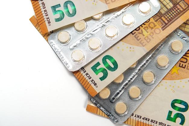 Compresse in blister e banconote da cinquanta euro isolate su bianco, costoso concetto di assistenza sanitaria e farmaci