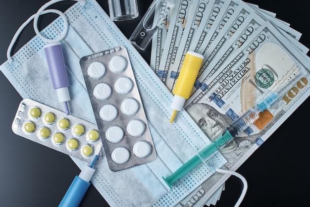 Compresse, maschera protettiva, articoli medici e banconote da un dollaro su sfondo scuro. concetto di medicina costoso. industria farmaceutica e assicurazione medica