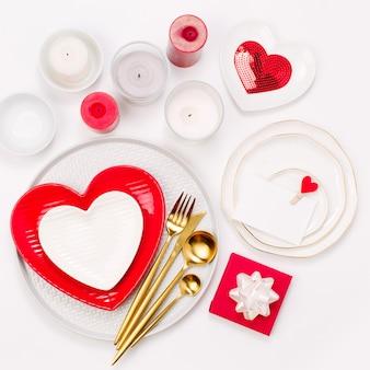 Stoviglie e decorazioni per servire una tavola festiva. piatti, bicchieri da vino e posate con tessuto decorativo su sfondo bianco.