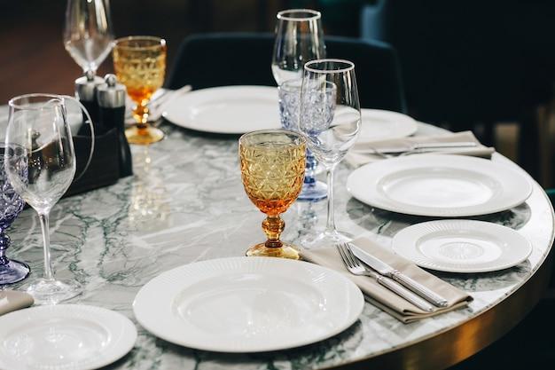Bicchieri da tavola, forchetta fiore, coltello servito per cena in un ristorante con interni accoglienti.