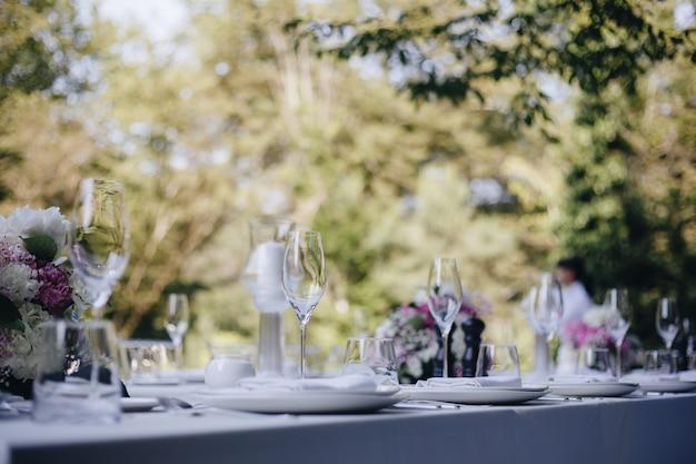 Bicchieri da tavola fiore forchetta coltello servito per cena in ristorante con interni accoglienti