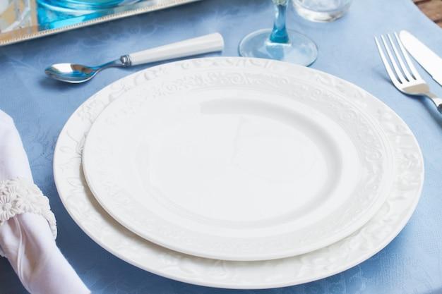 Servizio da tavola di piatti, tazze e utencil sulla tovaglia blu