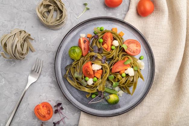 Tagliatelle verdi di spinaci con pomodoro, piselli e germogli microgreen su una superficie di cemento grigio e tessuto di lino