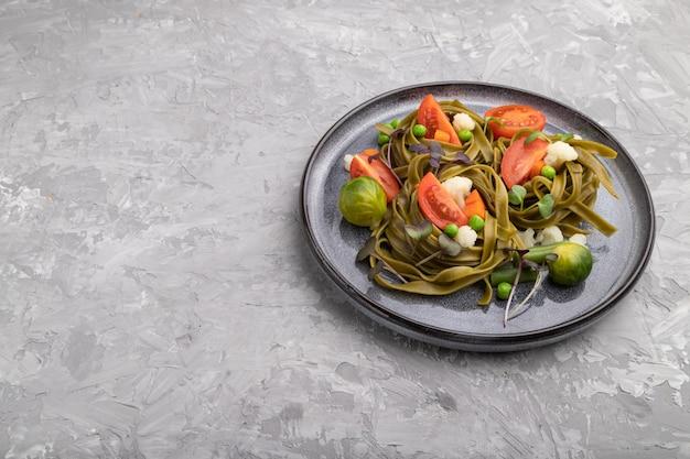 Tagliatelle di spinaci verdi con pomodoro, piselli e germogli microgreen su una superficie di cemento grigio