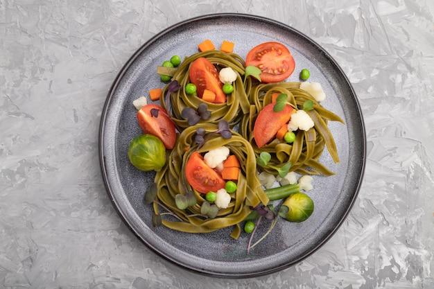 Tagliatelle verdi di spinaci con pomodoro, piselli e germogli microgreen su una superficie di cemento grigio