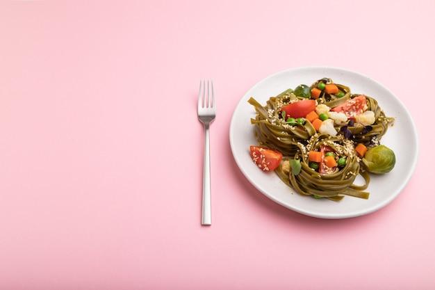 Tagliatelle di spinaci verdi con pomodoro, piselli e germogli microgreen su una superficie rosa pastello