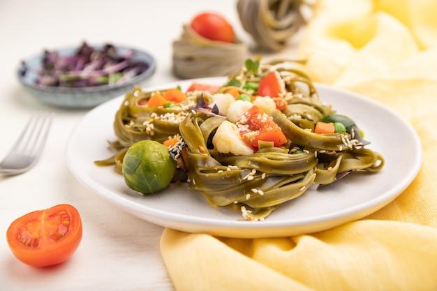 Tagliatelle di pasta verde agli spinaci con pomodoro, piselli e germogli microgreen su una superficie di legno bianca e tessuto giallo