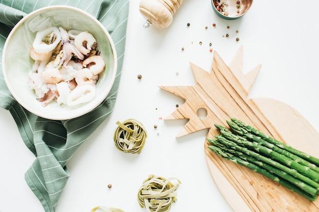 Tagliatelle ingredienti pasta pasta, frutti di mare, asparagi e pepe. disposizione piatta, vista dall'alto