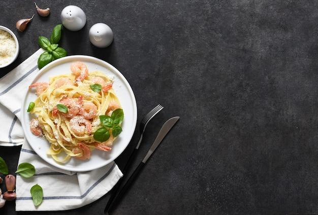 Tagliatelle con salsa cremosa, parmigiano e gamberetti in un piatto su uno sfondo nero. vista dall'alto.