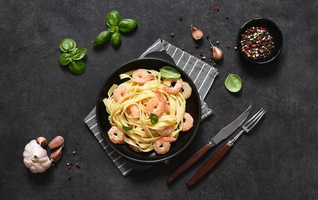 Tagliatelle con salsa cremosa e gamberetti in padella sul tavolo della cucina su uno sfondo nero. vista dall'alto.